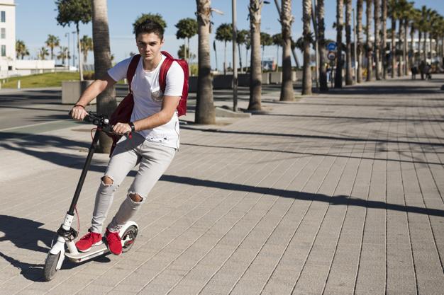 En dreng står på løbehjul
